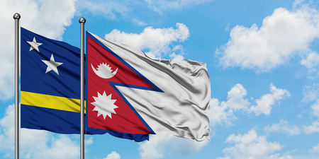 Curacao and Nepal flag waving in the wind against white cloudy blue sky together. Diplomacy concept, international relations.