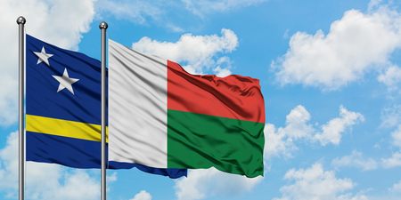 Curacao and Madagascar flag waving in the wind against white cloudy blue sky together. Diplomacy concept, international relations.