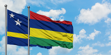 Curacao and Mauritius flag waving in the wind against white cloudy blue sky together. Diplomacy concept, international relations.