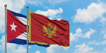 Cuba and Montenegro flag waving in the wind against white cloudy blue sky together. Diplomacy concept, international relations. Stock Photo