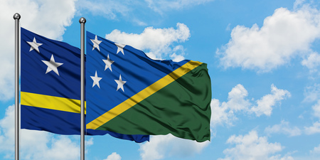 Curacao and Solomon Islands flag waving in the wind against white cloudy blue sky together. Diplomacy concept, international relations.