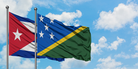 Cuba and Solomon Islands flag waving in the wind against white cloudy blue sky together. Diplomacy concept, international relations.