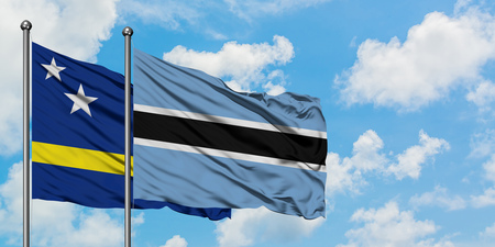 Curacao and Botswana flag waving in the wind against white cloudy blue sky together. Diplomacy concept, international relations.