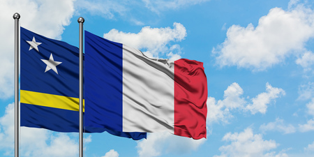Curacao and France flag waving in the wind against white cloudy blue sky together. Diplomacy concept, international relations. Stockfoto