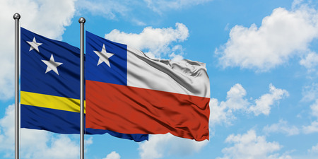 Curacao and Chile flag waving in the wind against white cloudy blue sky together. Diplomacy concept, international relations.
