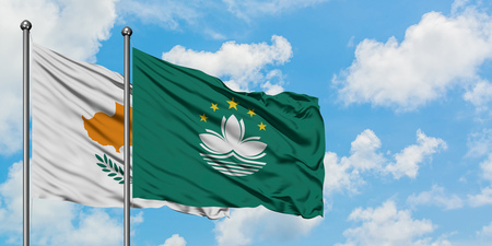 Cyprus and Macao flag waving in the wind against white cloudy blue sky together. Diplomacy concept, international relations.