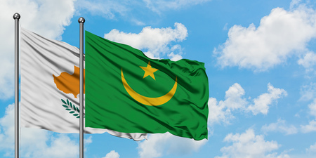 Cyprus and Mauritania flag waving in the wind against white cloudy blue sky together. Diplomacy concept, international relations.