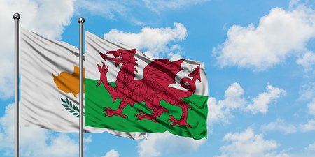 Cyprus and Wales flag waving in the wind against white cloudy blue sky together. Diplomacy concept, international relations. Standard-Bild