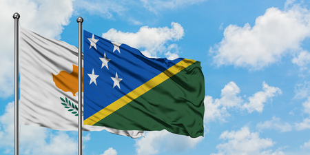 Cyprus and Solomon Islands flag waving in the wind against white cloudy blue sky together. Diplomacy concept, international relations. Stok Fotoğraf