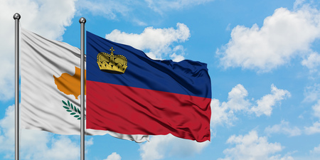 Cyprus and Liechtenstein flag waving in the wind against white cloudy blue sky together. Diplomacy concept, international relations.