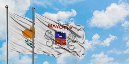Cyprus and Mayotte flag waving in the wind against white cloudy blue sky together. Diplomacy concept, international relations.