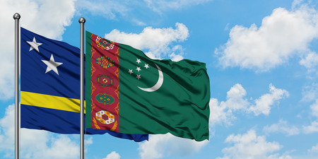 Curacao and Turkmenistan flag waving in the wind against white cloudy blue sky together. Diplomacy concept, international relations.