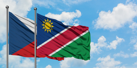 Czech Republic and Namibia flag waving in the wind against white cloudy blue sky together. Diplomacy concept, international relations.
