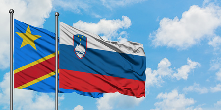 Congo and Slovenia flag waving in the wind against white cloudy blue sky together. Diplomacy concept, international relations.