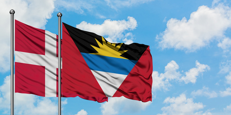Denmark and Antigua and Barbuda flag waving in the wind against white cloudy blue sky together. Diplomacy concept, international relations.