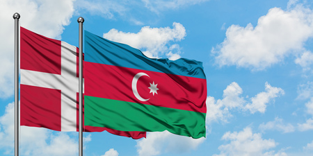 Denmark and Azerbaijan flag waving in the wind against white cloudy blue sky together. Diplomacy concept, international relations.