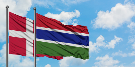 Denmark and Gambia flag waving in the wind against white cloudy blue sky together. Diplomacy concept, international relations.