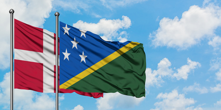 Denmark and Solomon Islands flag waving in the wind against white cloudy blue sky together. Diplomacy concept, international relations.