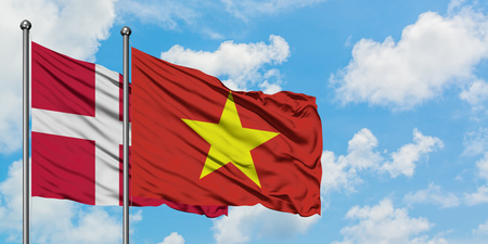 Denmark and Vietnam flag waving in the wind against white cloudy blue sky together. Diplomacy concept, international relations.