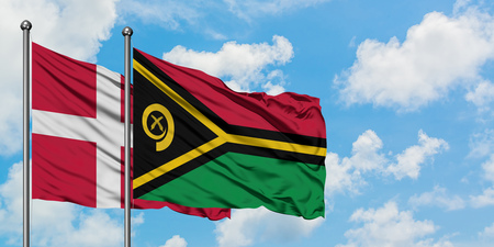 Denmark and Vanuatu flag waving in the wind against white cloudy blue sky together. Diplomacy concept, international relations.