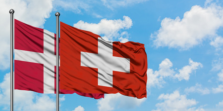 Denmark and Switzerland flag waving in the wind against white cloudy blue sky together. Diplomacy concept, international relations.