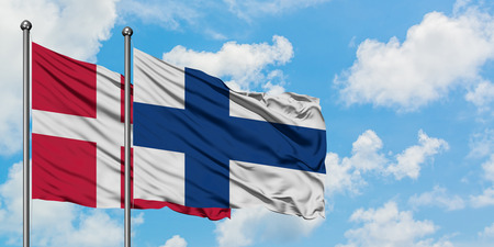 Denmark and Finland flag waving in the wind against white cloudy blue sky together. Diplomacy concept, international relations.