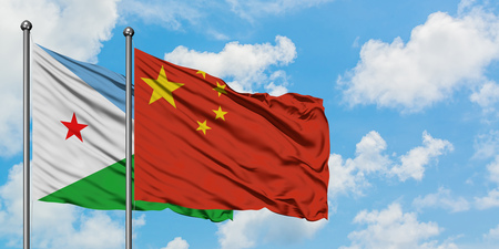 Djibouti and China flag waving in the wind against white cloudy blue sky together. Diplomacy concept, international relations. 版權商用圖片
