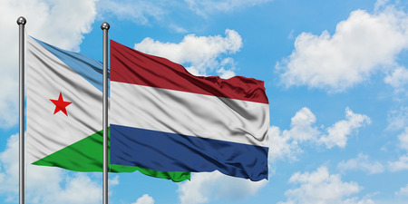 Djibouti and Netherlands flag waving in the wind against white cloudy blue sky together. Diplomacy concept, international relations.