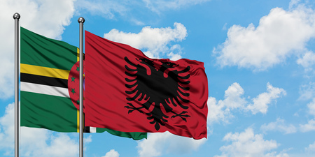 Dominica and Albania flag waving in the wind against white cloudy blue sky together. Diplomacy concept, international relations.