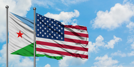 Djibouti and United States flag waving in the wind against white cloudy blue sky together. Diplomacy concept, international relations.