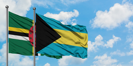 Dominica and Bahamas flag waving in the wind against white cloudy blue sky together. Diplomacy concept, international relations. Stock Photo - 123366180