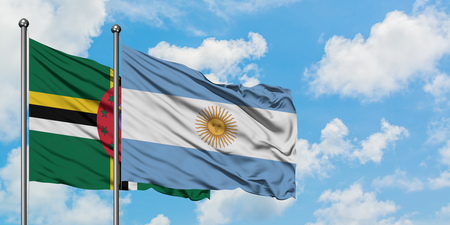 Dominica and Argentina flag waving in the wind against white cloudy blue sky together. Diplomacy concept, international relations. Stock Photo