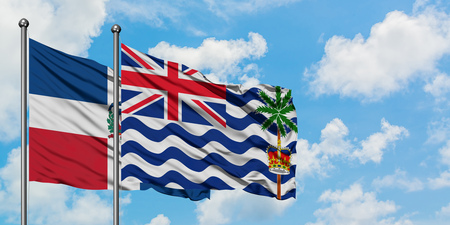 Dominican Republic and British Indian Ocean Territory flag waving in the wind against white cloudy blue sky together. Diplomacy concept, international relations.