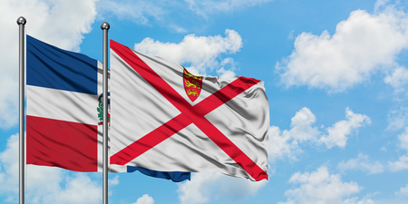 Dominican Republic and Jersey flag waving in the wind against white cloudy blue sky together. Diplomacy concept, international relations.