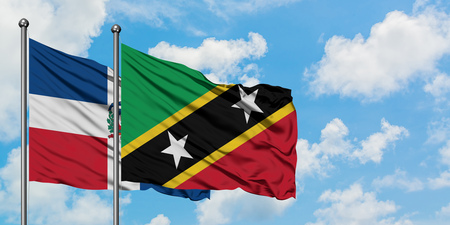 Dominican Republic and Saint Kitts And Nevis flag waving in the wind against white cloudy blue sky together. Diplomacy concept, international relations.