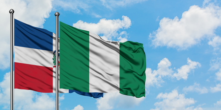Dominican Republic and Nigeria flag waving in the wind against white cloudy blue sky together. Diplomacy concept, international relations.