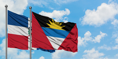 Dominican Republic and Antigua and Barbuda flag waving in the wind against white cloudy blue sky together. Diplomacy concept, international relations.