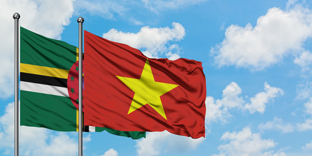Dominica and Vietnam flag waving in the wind against white cloudy blue sky together. Diplomacy concept, international relations. Stock Photo