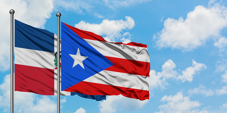 Dominican Republic and Puerto Rico flag waving in the wind against white cloudy blue sky together. Diplomacy concept, international relations.
