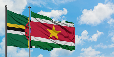 Dominica and Suriname flag waving in the wind against white cloudy blue sky together. Diplomacy concept, international relations.