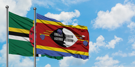 Dominica and Swaziland flag waving in the wind against white cloudy blue sky together. Diplomacy concept, international relations.
