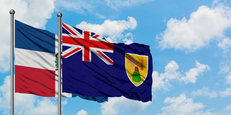 Dominican Republic and Turks And Caicos Islands flag waving in the wind against white cloudy blue sky together. Diplomacy concept, international relations.