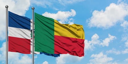 Dominican Republic and Benin flag waving in the wind against white cloudy blue sky together. Diplomacy concept, international relations.