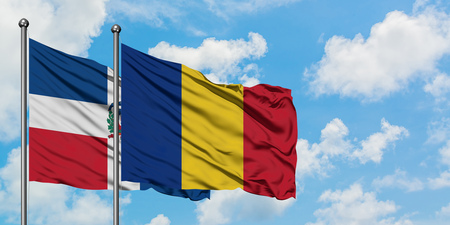 Dominican Republic and Romania flag waving in the wind against white cloudy blue sky together. Diplomacy concept, international relations.