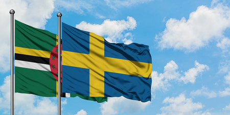 Dominica and Sweden flag waving in the wind against white cloudy blue sky together. Diplomacy concept, international relations.
