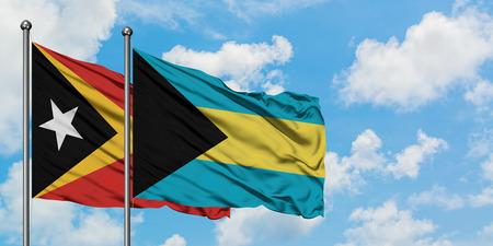 East Timor and Bahamas flag waving in the wind against white cloudy blue sky together. Diplomacy concept, international relations. Stock Photo - 123367748