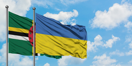 Dominica and Ukraine flag waving in the wind against white cloudy blue sky together. Diplomacy concept, international relations. Stock Photo