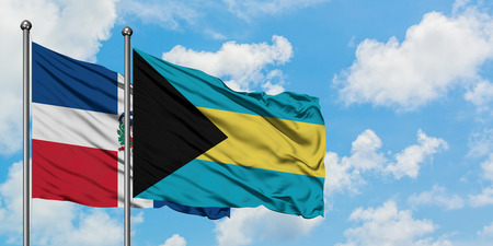 Dominican Republic and Bahamas flag waving in the wind against white cloudy blue sky together. Diplomacy concept, international relations. Stock Photo - 123367767