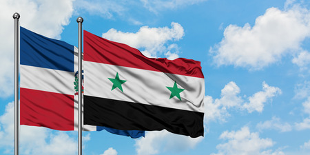 Dominican Republic and Syria flag waving in the wind against white cloudy blue sky together. Diplomacy concept, international relations.