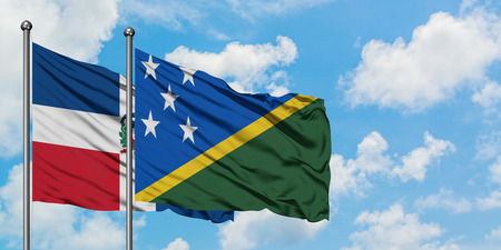 Dominican Republic and Solomon Islands flag waving in the wind against white cloudy blue sky together. Diplomacy concept, international relations.